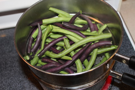 Green and purple beans in a pan.
